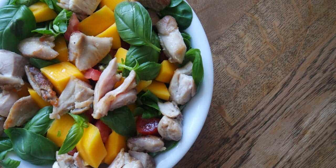 Groene salade met kippendijen en mango